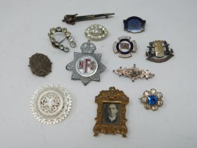 A collection of twelve antique brooches and badges. Including a carved mother of pearl brooch with
