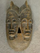 A carved hardwood Baule 'Twin Face Mask' from the Ivory Coast 37x20cm