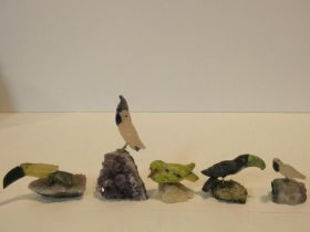 A collection of five carved bird figures from various gemstones standing on naturalistic quartz rock