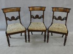 A set of three William IV mahogany dining chairs with figured veneer backrails and acanthus palmette