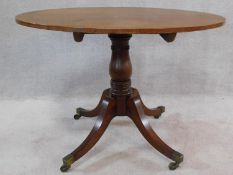 A 19th century mahogany tilt top tea table on swept quadruped supports terminating in brass cap