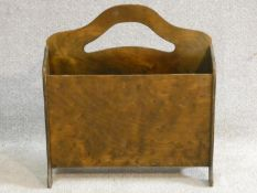 A mid century vintage laminated ply wood two section magazine basket with pierced cut carrying