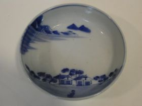 A Meji period blue and white ceramic Japanese bowl with hand painted village scene with mountains in