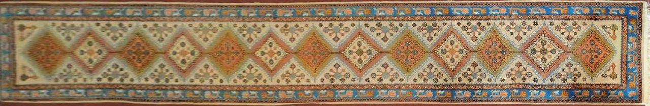 A Turkish Usak runner with repeating diamond medallions on a cream ground within an azure bird and