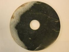 A Chinese jade disk with pierced circular central section. 31x31cm