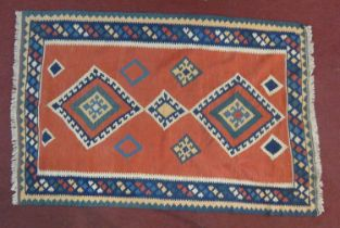 A Qashqai kelim rug with repeating diamond medallions on a terracotta field within geometric