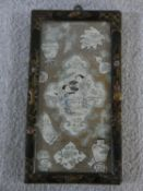 A Chinese silk embroidered panel with central figures in a landscape surrounded by urn, scroll and