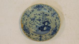 An antique blue and white floral design glazed hand painted ceramic plate. It has a bright yellow