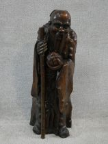 A Ming dynasty carved Chinese root wood sculpture of an immortal, an elderly man holding a staff and