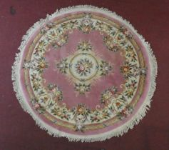 A woollen Chinese style carpet with floral decoration on a blush ground. D.208cm