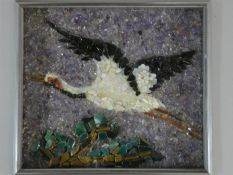 A Japanese framed gemstone pebble mosaic of a Red Crowned Crane flying over trees, set with