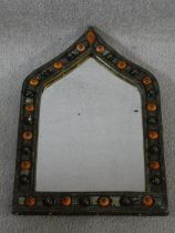 An Indian brass and metal mirror with moulded orange and black bead studded detailing and repousse