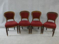 A set of four Victorian mahogany hooped back dining chairs in burgundy velour upholstery on reeded