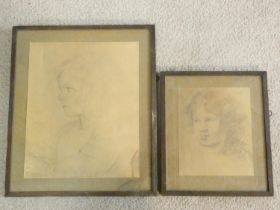 A framed and glazed print of a pencil sketch, portrait of a child and another similar print.
