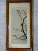 An early 20th century framed and glazed Japanese silk embroidery, a bird in flight with blossom on