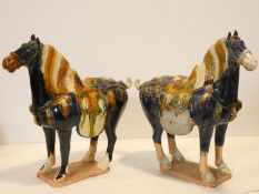 Two Tang style ceramic horse figures in blue and ochre glaze. H.37 W.40 D.14cm