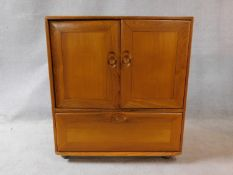 A vintage elm Ercol cabinet with panel doors and drop down base door fitted for HI Fi. H.94xW.85xL.