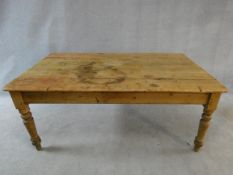 A Victorian pine kitchen dining table with planked top and end drawer on turned tapering supports.
