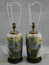 A pair of Chinese style table lamps of fluted baluster form in decorative floral glaze resting on