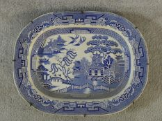 A large antique Staffordshire stoneware blue and white willow pattern transferware design meat