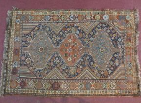 A Kashkai rug with triple pole medallions on midnight ground contained within burgundy stylised
