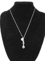 An 18 carat white gold pearl and diamond articulated pendant on a 9ct white gold fancy link chain.