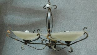 A wrought metal framed three branch ceiling chandelier with floral decorated opaque shades 50x75cm