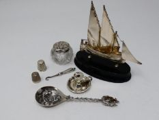 A collection of silver and white metal items. Including a Maltese articulated sailing ship on an