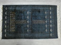 An Eastern rug with repeating floral motifs on an enamel blue ground within geometric border.
