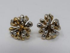 A pair of 9ct yellow and white gold and diamond stylised floral stud earrings. Each earring is set