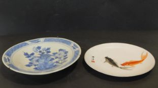 Two antique hand painted Oriental ceramic plates. One with a blue and white floral design with a