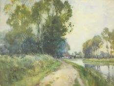 A framed and glazed watercolour, towpath by a canal with houses in distance, indistinctly signed.