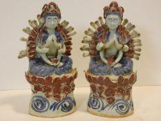 A pair of Eastern ceramic glazed figures of the goddess Vasudhara seated on floral lotus leaf