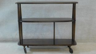 An elm Ercol trolley bookcase, model 361 on industrial style casters. H.76 W.92 D.32cm