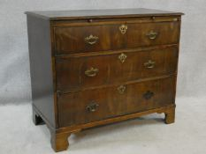 A Georgian walnut chest of three long drawers fitted with brushing slide raised on ogee bracket