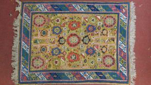 An Eastern rug with all over stylised floral motifs on a sand ground contained by geometric multi