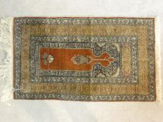 An Eastern prayer mat with floral design on burgundy ground contained within geometric multi