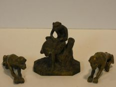 An antique brass monkey figure sitting on a tree stump with another below and a pair of brass