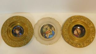 A pair of Continental brass chargers with hand painted central portraits on porcelain panels along