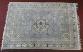 A Chinese carpet with central floral medallion on pale ground contained by spandrels decorated