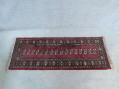 A Bokhara rug with repeating gul motifs on burgundy ground within stylised floral borders. 187x76cm
