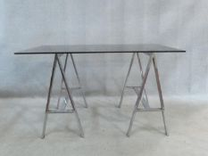 A 1970's vintage side table with smoked plate glass top resting on chrome trestles. H.73 W.128 D.