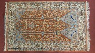 A large Persian style prayer rug with all over floral decoration on a rouge ground within stylised