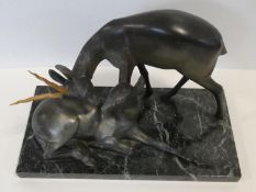A pair of spelter Art Deco male and female gazelles mounted on a black and white veined marble base.