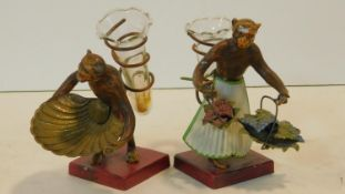 A pair of vintage cold painted cast metal monkey figures each carrying a trumpet shape glass spill