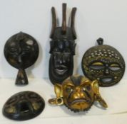 A carved and gilded Chinese monkey god face mask along with four carved African tribal masks. H.58cm