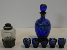 A cobalt blue glass decanter and shot glasses with painted silver floral design along with a