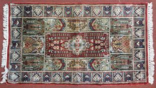 A Bachtiar rug with central pole medallion on burgundy ground within floral panels. 62x112cm