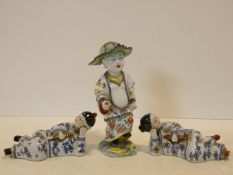 An antique hand painted Oriental figure with leaf hat and in traditional robe, intricately decorated