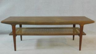 A 1970's vintage teak coffee table on tapering supports united by caned undertier. H.47 W.137 D.46cm